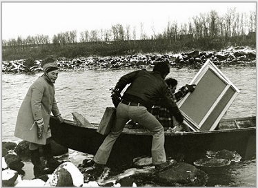 Photo of Bier Ante Ris'ten (left); Ronald Davis (center) with paint box and portable easel; and Stanley Roseman (right) with his canvases as they prepare to cross a river in a rowboat in Lappland, 1976. Photo courtesy of Myrdene Anderson.